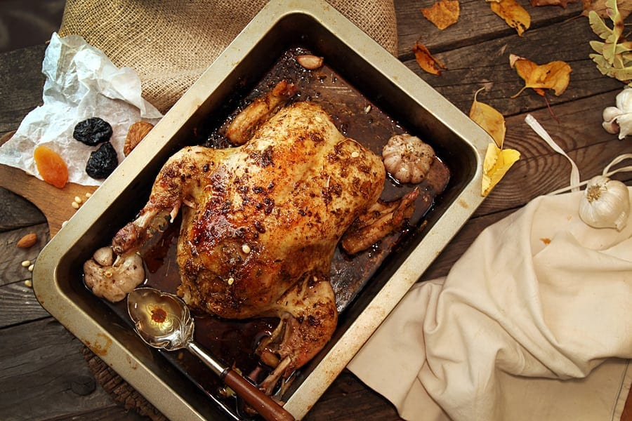 Roasted small turkey for celebration Thanksgiving day in roasting pan on old rustic wooden table. Stuffed with couscous with a fig prunes dried apricots almonds and pine nuts