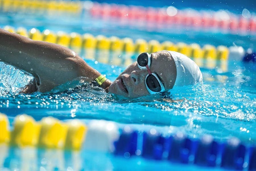 Close-up photo of female swimmer in the motion in the swimming pool outdoors. She wears a black-lime swimsuit, a white swim cap and swim glasses. Girl looks into the camera. Horizontal.