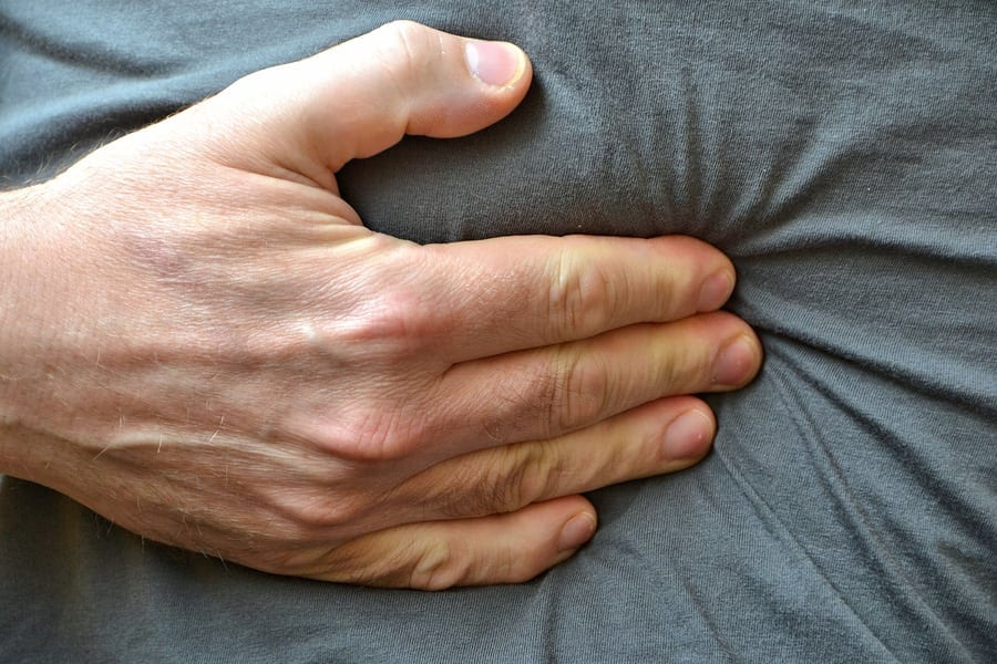 A man with abdominal pain, grabs her in the stomach